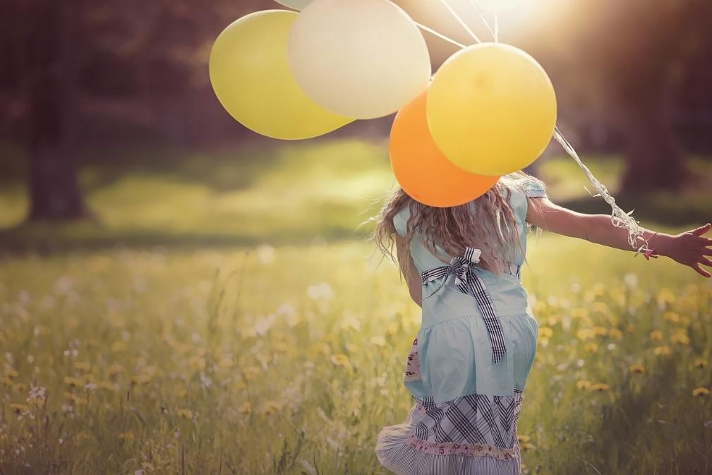 niña con globos en la mano