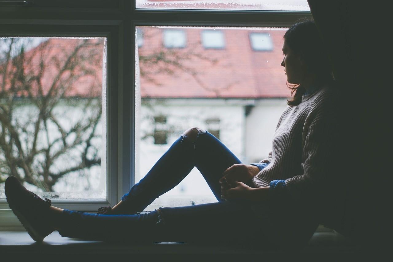 Imagen que contiene ventana, mujer, pensativa